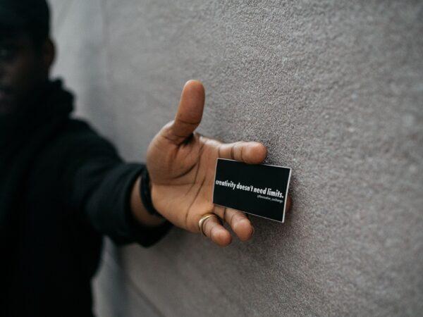 wizytówka z napisem trzymana w dłoni na tle szarej ściany