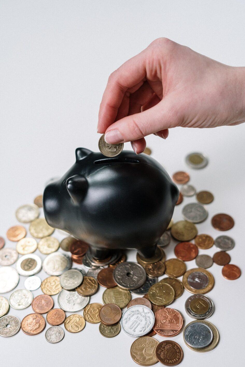 osoba wrzucająca monetę do skarbonki